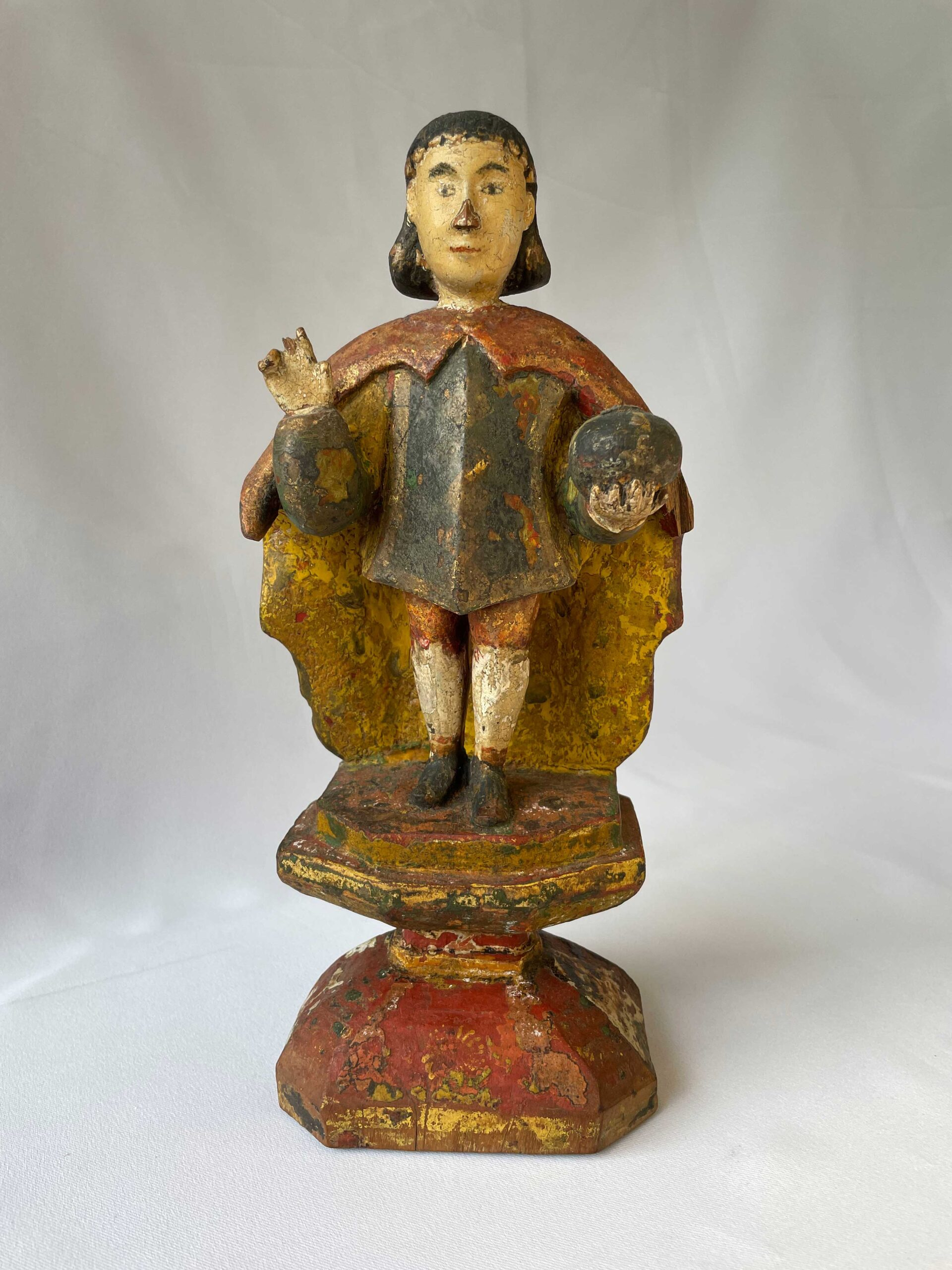 """A folk rendition of the Santo Niño of Cebu from Bohol Island. Santos from Bohol are excellent study pieces for colonial polychromy. They would paint their santos in layers of paints in extravagant colors sourced from plants, insects, mollusks, minerals and other natural pigments until synthetic pigments became available by late 19th to early 20th century. In Fernando Zobel's seminal essay """"Philippine Colonial Sculpture"""" (1958), he noted that one of the distinct characteristics of Philippine colonial santos that distinguishes them from European and South American statuaries is our preference for colours, which he described as """"wild,"""" """"blindingly strong,"""" and """"strikingly original.""""   (From the Emil Marañon III collection)"""